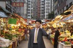 Бизнесмен используя сотовый телефон на уличном рынке Стоковое Изображение