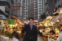 Бизнесмен используя сотовый телефон на уличном рынке Стоковые Фото