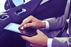 Бизнесмен используя таблетку в автомобиле Стоковое Фото