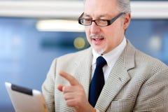 Бизнесмен используя таблетку в его офисе стоковое изображение rf