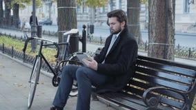 Бизнесмен используя таблетку сидя на стенде около велосипеда сток-видео