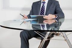 Бизнесмен используя таблетку цифров в офисе Стоковое Изображение RF