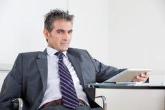 Бизнесмен используя таблетку цифров в офисе Стоковые Фотографии RF