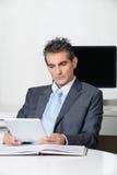 Бизнесмен используя таблетку цифров на столе Стоковые Фото