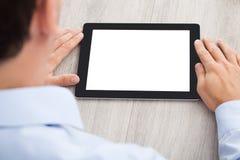Бизнесмен используя таблетку цифров на столе Стоковое Фото