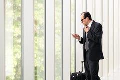 Бизнесмен используя телефон близко к большим окнам Стоковое Изображение RF