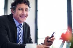 Бизнесмен используя телефон пока работающ на компьтер-книжке Стоковое Фото