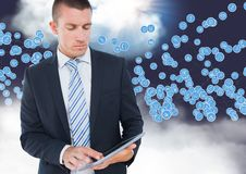 Бизнесмен используя цифровую таблетку против значков технологии в небе стоковое изображение