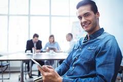 Бизнесмен используя цифровую таблетку против коллег в конференц-зале Стоковые Изображения RF