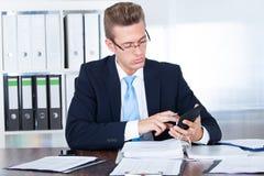 Бизнесмен используя чалькулятор Стоковое Изображение