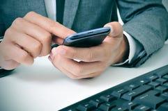 Бизнесмен используя smartphone в офисе стоковое фото