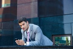 Бизнесмен используя smartphone outdoors Стоковое Изображение