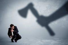 Бизнесмен испуганный огромной руки тени держа концепцию оси Стоковое Фото