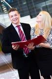 Бизнесмен и бизнес-леди говоря над документами Стоковые Фотографии RF