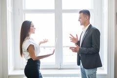 Бизнесмен и бизнес-леди обсуждают неофициальное около окон офисного здания стоковое фото rf