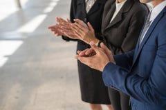 Бизнесмен и бизнес-леди хлопают их руки для того чтобы поздравить подписание согласования или контракта между их компаниями Стоковые Фотографии RF