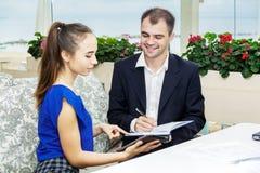 Бизнесмен и его секретарша работая совместно дневник делает примечания человека Стоковое фото RF