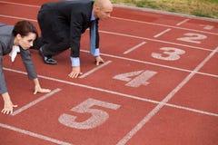 Бизнесмен и женщина на линии старта идущего следа Стоковое фото RF