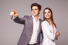 Бизнесмен и женщина на серой предпосылке Человек указанный прочь на серый цвет стоковое фото rf