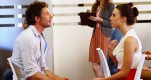 Бизнесмен и женщина обсуждая друг с другом в встрече акции видеоматериалы