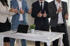 Бизнесмен и женщина показывая большие пальцы руки до руководителя потому что succe Стоковая Фотография