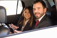 Бизнесмен и женщина работая в автомобиле Стоковые Изображения RF
