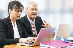 Бизнесмен и женщина работая на компьтер-книжке Стоковые Фотографии RF