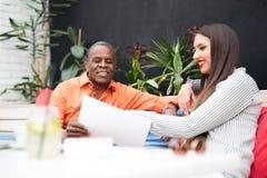 Бизнесмен и женщина сидя в кафе и обсуждая контракт Стоковая Фотография