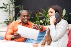 Бизнесмен и женщина сидя в кафе и обсуждая контракт Стоковое фото RF