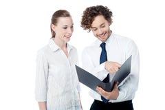 Бизнесмен и женщина смотря папку Стоковые Фото