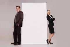 Бизнесмен и женщина стоя над пустым знаменем Стоковое Изображение
