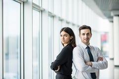 Бизнесмен и женщина стоя спина к спине с улыбками на их сторонах против панорамного окна Стоковое Изображение