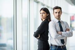Бизнесмен и женщина стоя спина к спине с улыбками на их сторонах против панорамного окна Стоковая Фотография RF