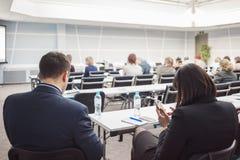 Бизнесмен и женщина с и люди слушая на конференции или на тренировке в зале Стоковое Изображение RF