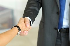 Бизнесмен и женщина трясут руки как здравствуйте! в крупном плане офиса Стоковые Изображения RF