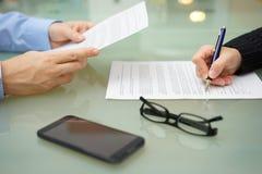 Бизнесмен и женщина читающ и подписывающ контракт Стоковые Фото