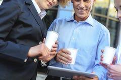 Бизнесмен и женщины выпивая напиток снаружи Стоковое Фото