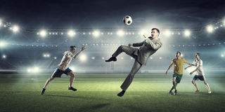 Бизнесмен и игроки воюя для шарика Стоковые Изображения