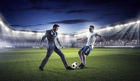 Бизнесмен и игрок воюя для шарика Стоковые Изображения RF