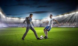 Бизнесмен и игрок воюя для шарика Стоковые Фото