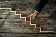 Бизнесмен или студент идя его пальцы вверх по деревянным шагам стоковое изображение
