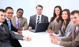 Бизнесмен и команда дела сидя на столе Стоковое Фото