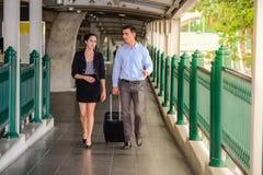 Бизнесмен и коммерсантка говорят и идут вместе с черным багажом на общественной улице, деловыми поездками Стоковое фото RF