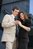 Бизнесмен и коммерсантка держа франтовской телефон Стоковые Изображения