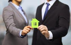 Бизнесмен и коммерсантка держа зеленый дом стоковые изображения