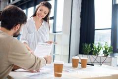 Бизнесмен и коммерсантка держа контракт и обсуждая в офисе мелкого бизнеса Стоковые Изображения