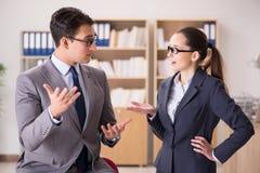 Бизнесмен и коммерсантка имея обсуждение в офисе Стоковые Изображения