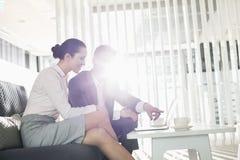 Бизнесмен и коммерсантка обсуждая над компьтер-книжкой в офисе Стоковая Фотография RF