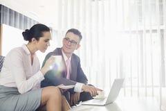 Бизнесмен и коммерсантка обсуждая над компьтер-книжкой в офисе Стоковые Изображения RF