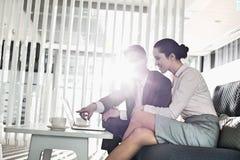 Бизнесмен и коммерсантка обсуждая над компьтер-книжкой в офисе Стоковое фото RF